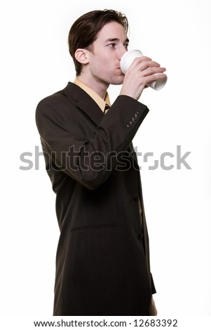 Young man wearing business suit drinking from a paper coffee cup standing on white