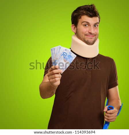 Young Man Wearing Cervical Collar Holding Euro Note Isolated On Green Background - stock photo