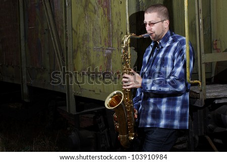 Young man wearing checked shirt playing the saxophone at an old train outdoors - stock photo