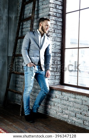 young man wearing elegant suit  near the window - stock photo