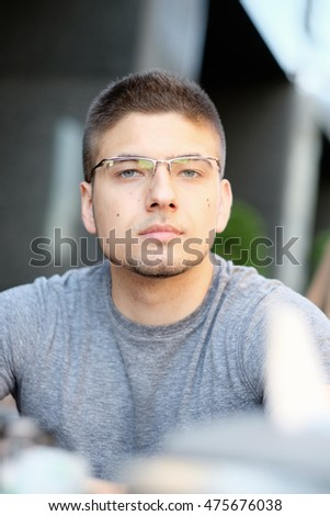 Young man wearing eyeglasses in outdoor restaurant