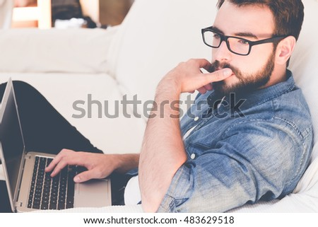 Young man wearing glasses using a laptop. Dressed casually in jeans. Bright crisp post processed. Urban life style, technology, online, business, shopping, fashion and job hunting concept.