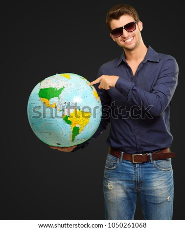 Young Man Wearing Goggle Showing Destination On Black Background