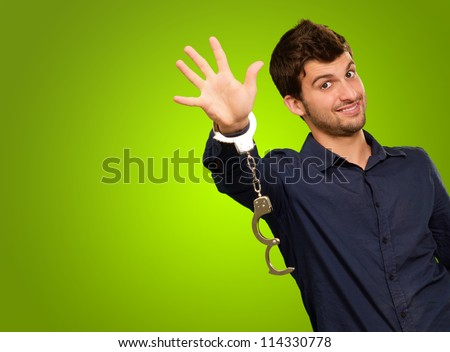 Young Man Wearing Handcuffs On Green Background - stock photo