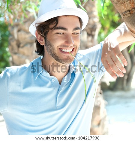 Young man wearing hat and casual clothes in sunny day. Leaning on palm tree at summer park - stock photo