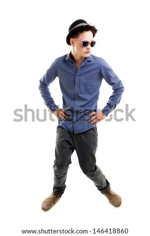 Young man wearing hat and sunglasses, with a seroius attitude,hands on hips,  knees bent, full lenght, isolated on white