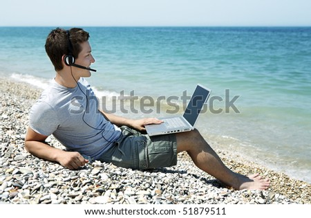 Young man wearing headset sitting on pebbled beach with laptop - stock photo