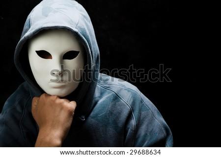 young man wearing mask and hood, studio shot - stock photo