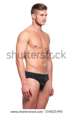 young man wearing nothing but his underware and looking away from the camera, isolated on white - stock photo