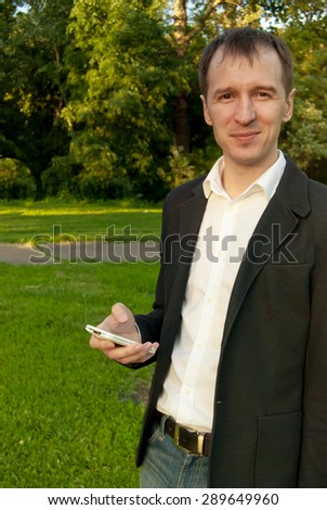 Young man wearing suit with smartphone smiling, outdoors on the green background of trees and bushes. Business man in a green zone or park. An image for topics of finance, business and communication