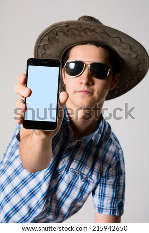 Young man wearing sunglasses and a hat in his hand phone shows. - stock photo