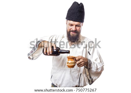 young man wearing traditional romanian costume on white background holding a botle of wine
