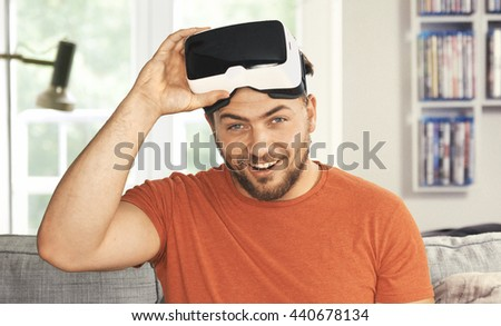Young man wearing virtual reality goggles. His livingroom transforms into VR space - Analog Film emulation-style