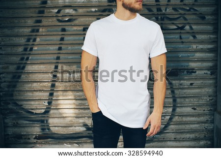 Young man wearing white blank t-shirt and blue jeans, standing on the street - stock photo