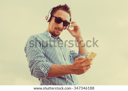 Young man wearing white blank t-shirt and blue jeans, standing on the street, guy with a beard in sunglasses shirt and shorts listening to music in headphones on a smartphone,iphone device,periscope  - stock photo