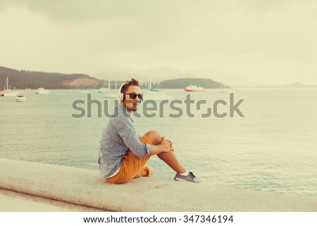 Young man wearing white blank t-shirt and blue jeans, standing on the street,young guy with sunglasses shirt and shorts listening to music in headphones on a smartphone on the pier near the sea - stock photo