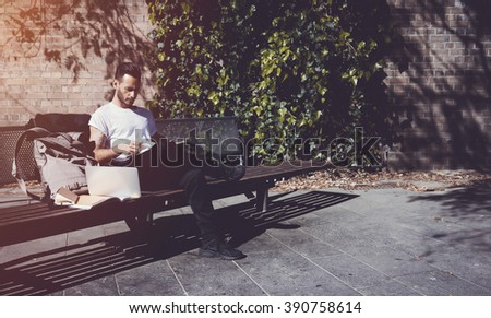 Young man wearing white tshirt sitting city park and reading book. Studying at the University, working new project. Books, laptop, backpack bench. Horizontal,  film effect - stock photo