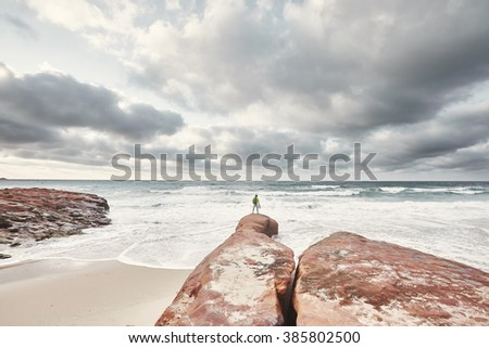 Young man wearing yellow jacket and green backpack, holding motorcycle helmet in his hand, standing on red rocky shore and enjoying view of stormy ocean under cloudy sky - exploring concept - stock photo