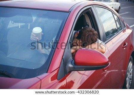 Young man while driving drinks cofee, bored in traffic - stock photo