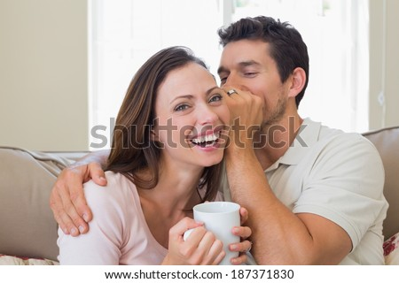 Young man whispering secret into a cheerful young womans ear in the living room at home - stock photo