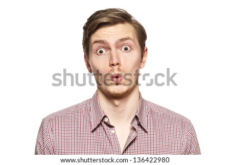 Young man whistles. Studio shot. Funny face. - stock photo
