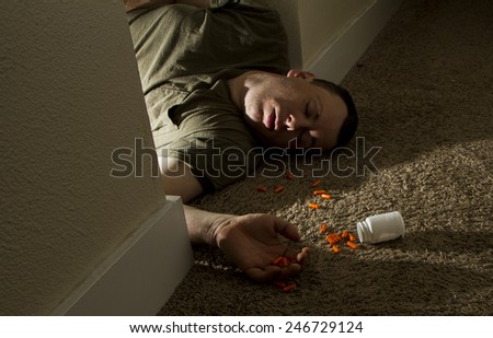 Young man who just killed himself laying on the ground next to a bottle of pills - stock photo