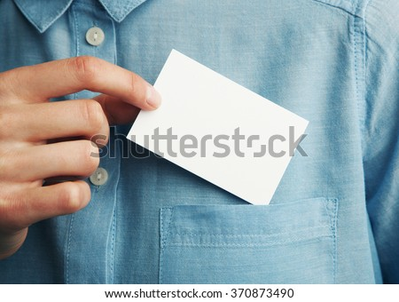 Young man who takes out blank business card from the pocket of his shirt - stock photo