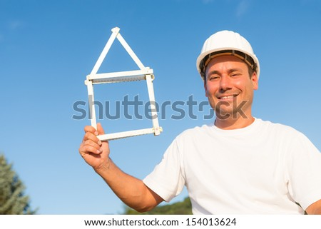 Young man who uses a measure to form his dream house - stock photo