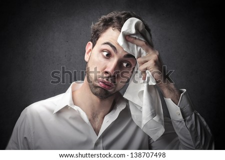 young man wipes sweat from his forehead with a handkerchief - stock photo