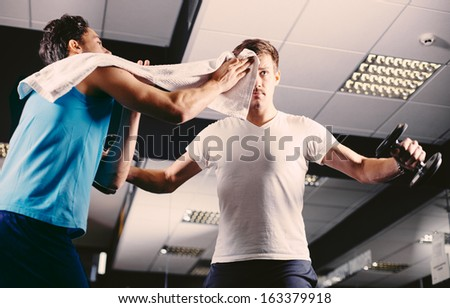 Young man wiping sweat off of friend's face in gym - stock photo