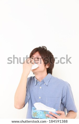 young man with a allergy sneezing into tissue