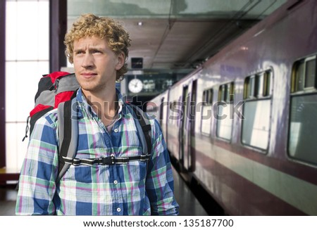 Young man with a backpack ready to embark on a journey by train - stock photo