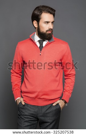 Young man with a beard and a cardigan and trousers, standing in the studio - stock photo