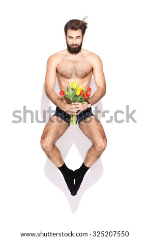 Young man with a beard and flowers jumping in the studio - stock photo