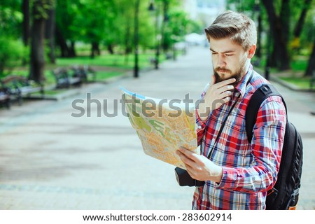 Young man with a beard holding a map and seriously thinking, outdoors in the alley of the park - stock photo