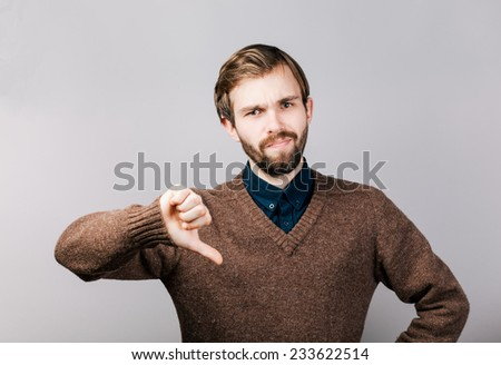young man with a beard in brown sweater showing thumbs down sign