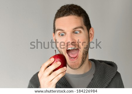 Young man with a beard looking to an apple with open mouth
