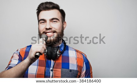 young man with a beard wearing a shirt holding a microphone - stock photo