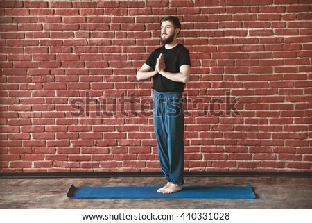 Young man with a beard wearing black T-shirt doing yoga position on blue matt at wall background, copy space, portrait, namaste asana. - stock photo