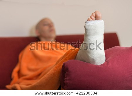 Young man with a broken ankle and a white cast on his leg, lying down on a red couch, covered with an orange comforter (selective focus) - stock photo