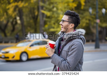Young man with a cup of coffee in New York city, taxi passing by. - stock photo