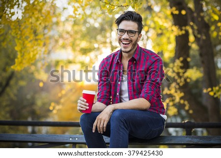 Young man with a cup of coffee. New York city, Central Park in an autumn day. - stock photo