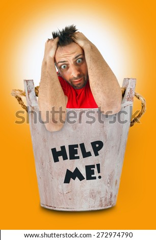 Young man with a desperate expression in wooden bucket. - stock photo