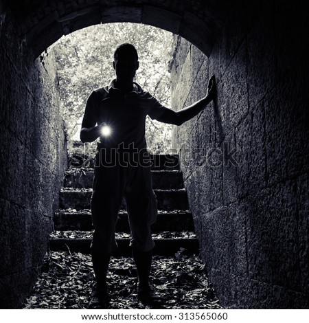 Young man with a flashlight enters the stone tunnel and looks in the dark, square photo - stock photo