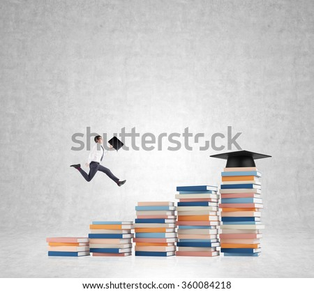 Young man with a folder in hand running up stairs made of piles of books of different size, graduation hat on the highest, concrete background. Concept of higher education. - stock photo