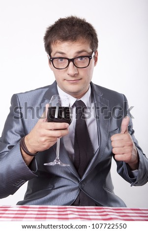 Young man with a glass of wine showing thumb up. - stock photo