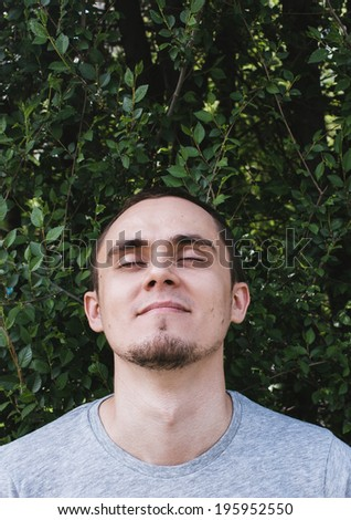 Young man with a goatee beard and a peaceful serene expression closing his eyes in bliss as he tilts his head back with a smile of pleasure against a leafy tree with copyspace - stock photo