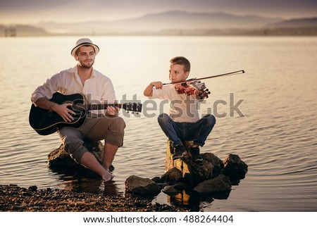 young man with a guitar and a boy with a red violin playing on the seashore