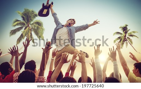 Young Man with a Guitar Performing on a Beach Concert - stock photo