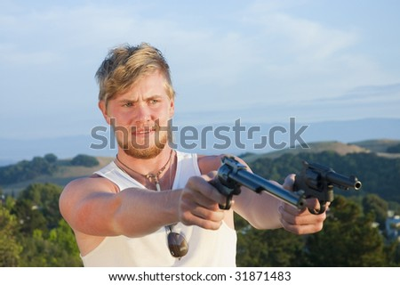 young man with a guns pointed towards viewer